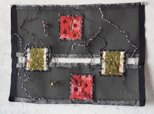 Black plastic mesh, quilt patches, ribbon and beads - yowza!
